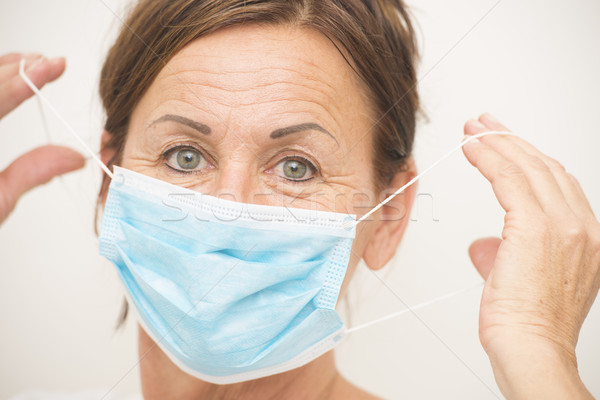 Nurse or doctor with mask over face Stock photo © roboriginal