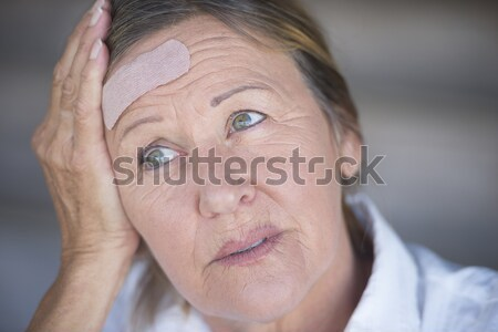 Stressed woman with band aid on forehead Stock photo © roboriginal