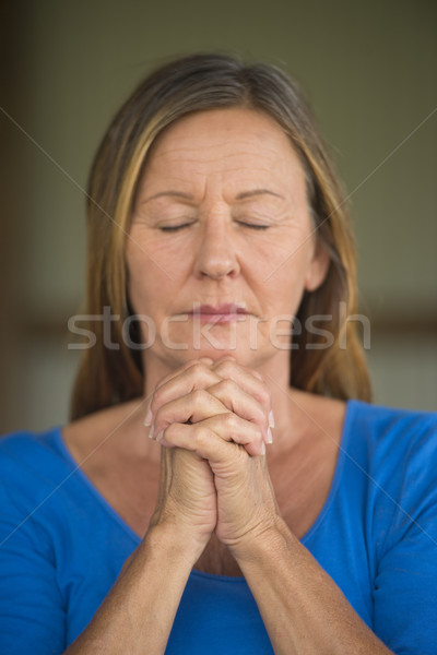 Woman praying with closed eyes concentrated Stock photo © roboriginal
