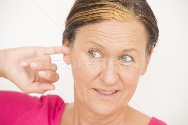 Stressed senior woman finger in ear Stock photo © roboriginal