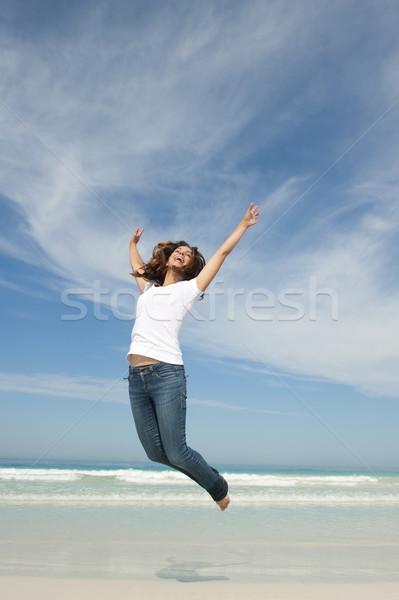 Happy pretty woman jumping for joy at beach Stock photo © roboriginal