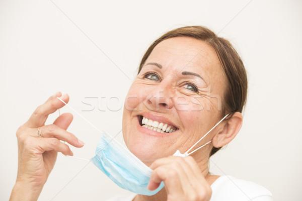 Happy female nurse with mask on white Stock photo © roboriginal