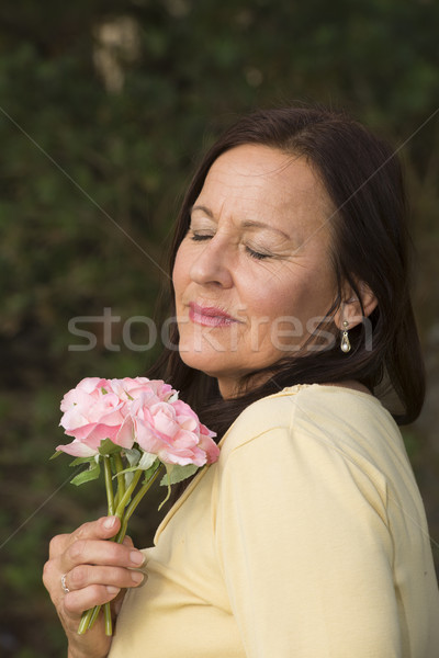 Mature Woman in love with rose Stock photo © roboriginal