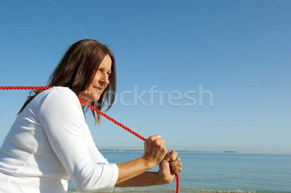 Woman pulling rope ocean background Stock photo © roboriginal