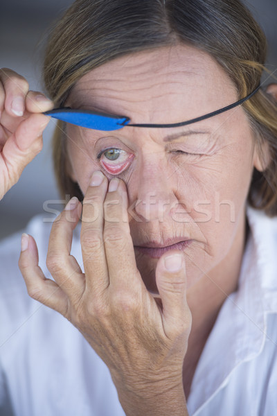 Stock photo: Injured woman lifting eye patch portrait
