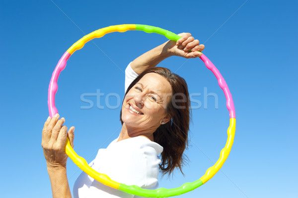 Active senior woman hula hoop exercise Stock photo © roboriginal
