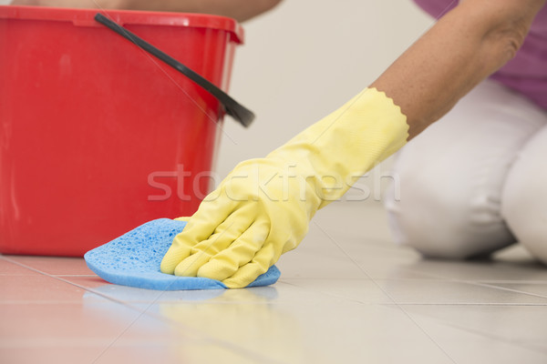 Cleaning floor tiles with glove and sponge Stock photo © roboriginal