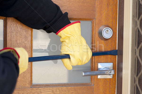 Burglar breaking in house with crowbar at door Stock photo © roboriginal
