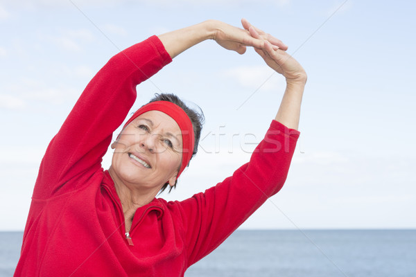 Mature woman stretching exercise ocean  Stock photo © roboriginal