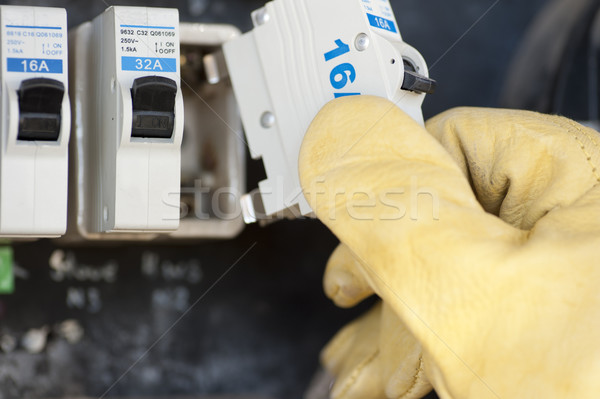 Electrician with electric fuse at switch board Stock photo © roboriginal