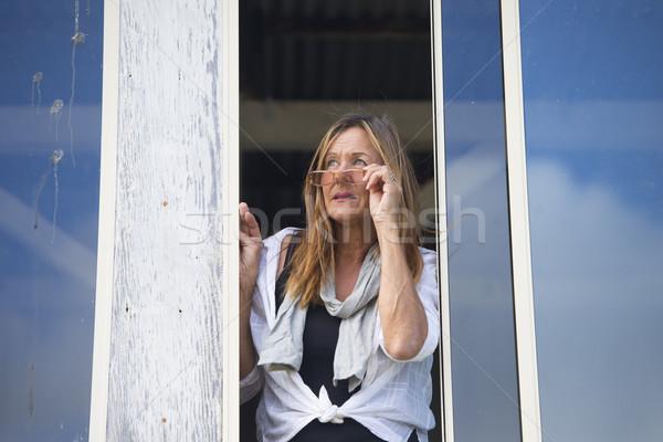 Woman observing from window outdoor Stock photo © roboriginal