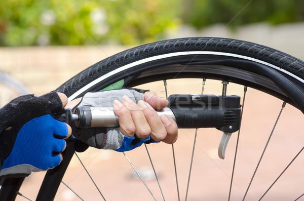 Stock photo: Pumping up flat bike tyre