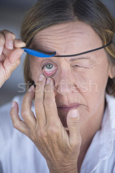 Stock photo: Suffering woman lifting eye patch portrait