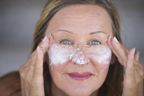 Confident mature woman face creme skin care Stock photo © roboriginal