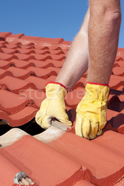 Worker replacing roof tiles on house Stock photo © roboriginal