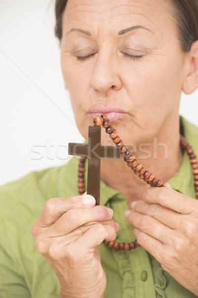 Religious woman kissing christian crucifix Stock photo © roboriginal