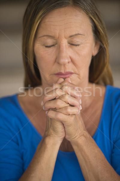 Rijpe vrouw bidden gevouwen handen aantrekkelijk Stockfoto © roboriginal