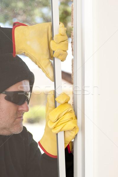 Thief breaking through window of home Stock photo © roboriginal