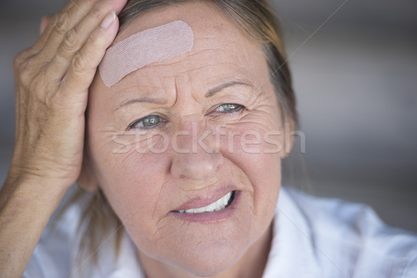 Woman with painful headache and band aid Stock photo © roboriginal