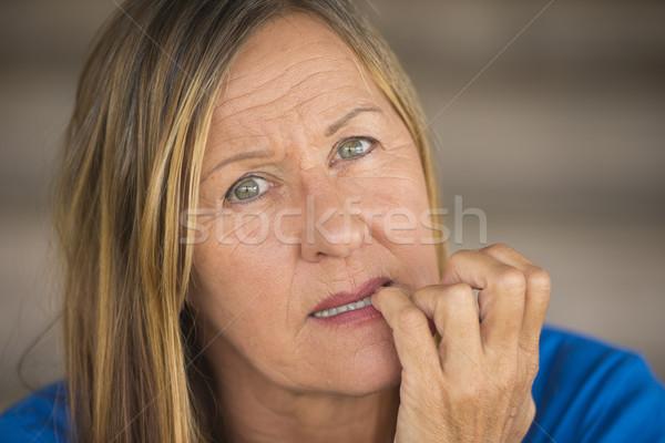 Insecure woman biting finger nails Stock photo © roboriginal