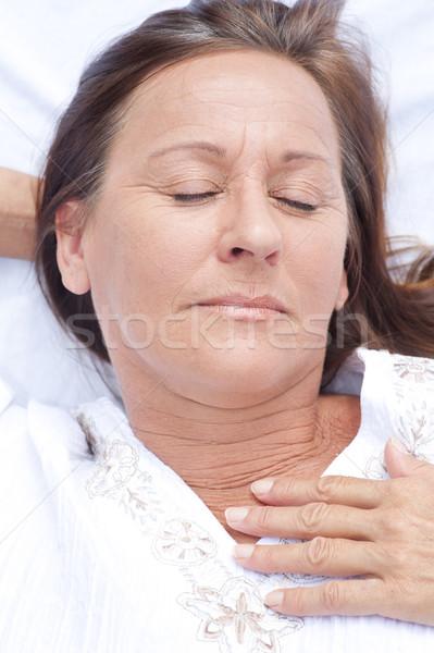 Happy mature woman asleep in bed Stock photo © roboriginal