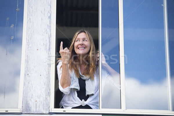 Cheeky happy woman at window finger signal Stock photo © roboriginal