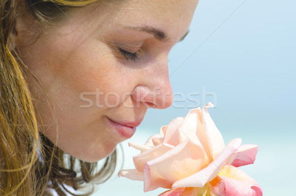 Stock photo: Pretty young girl smelling scent of flower