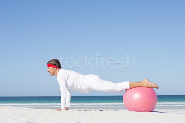 Mature woman yoga exercise beach Stock photo © roboriginal