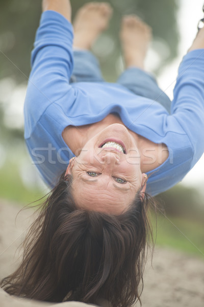 Attractive mature woman on swing upside down Stock photo © roboriginal