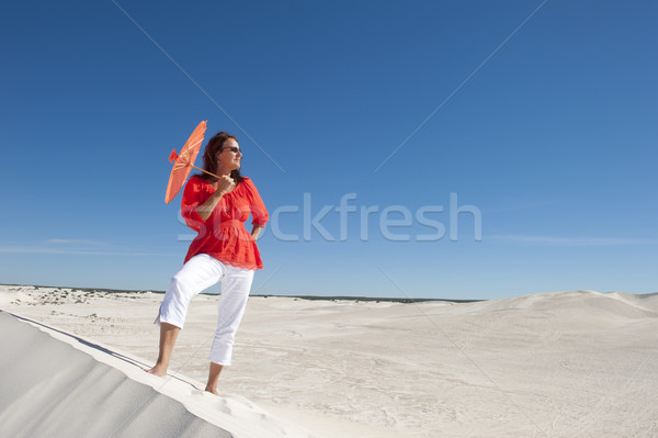 Attractive woman with umbrella on desert sand dune Stock photo © roboriginal