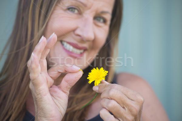 Woman plugging petal of yellow flower Stock photo © roboriginal