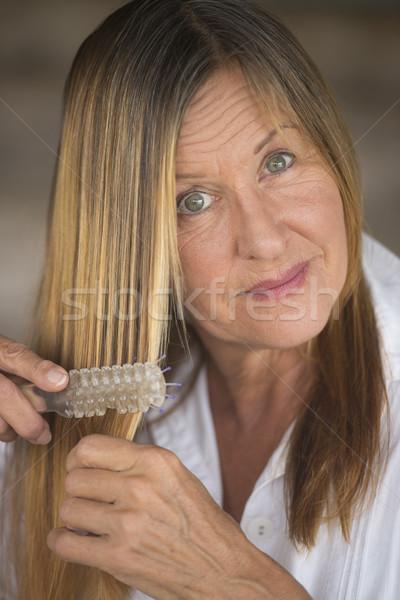 Elegant woman brushing long hair Stock photo © roboriginal