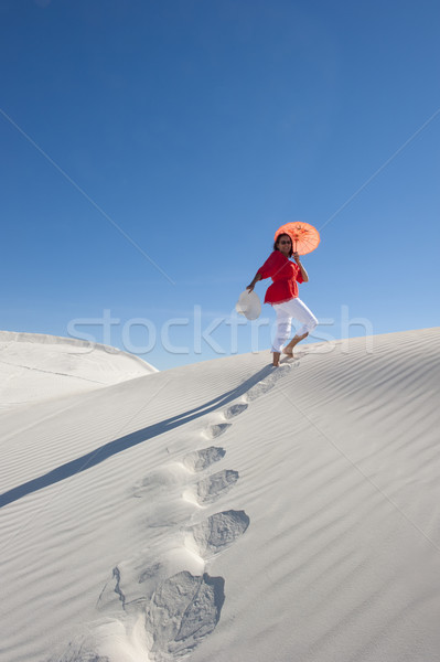 Attractive woman leaving footsteps up a sanddune Stock photo © roboriginal