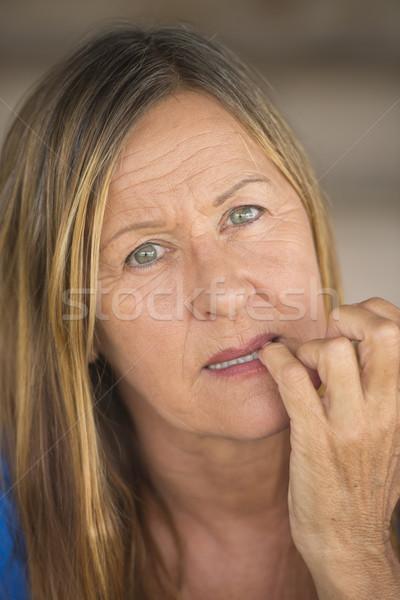 Insecure woman biting nervous finger nails Stock photo © roboriginal