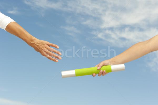 Hands reaching baton for teamwork Stock photo © roboriginal
