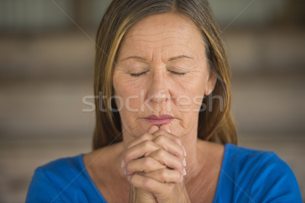Woman praying closed eyes folded hands Stock photo © roboriginal