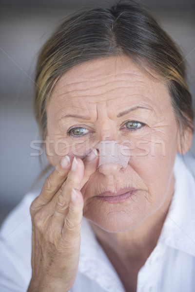 Mature woman with band aid on injured nose Stock photo © roboriginal