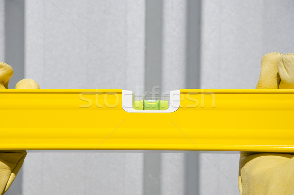 Stock photo: Hands with gloves on spirit level metal background