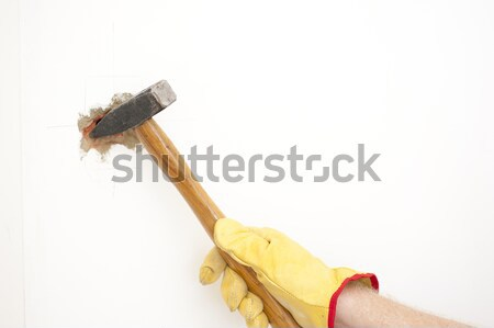 Hammer smashing hole in white house wall Stock photo © roboriginal