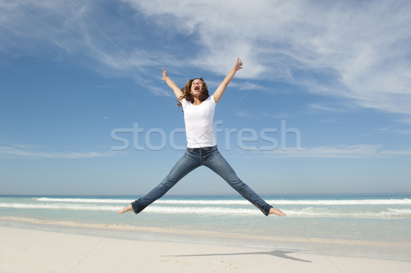 Cheerful happy young woman jumping at beach Stock photo © roboriginal
