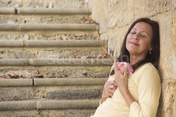 Happy mature woman in love with rose Stock photo © roboriginal
