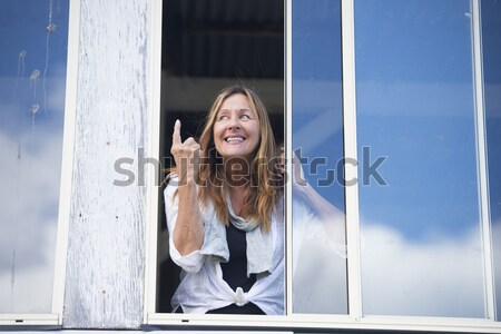 Happy relaxed Woman waving hand at window Stock photo © roboriginal