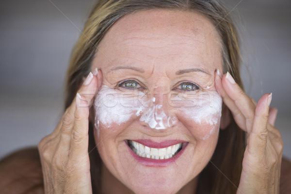 Joyful mature woman face creme skin care Stock photo © roboriginal