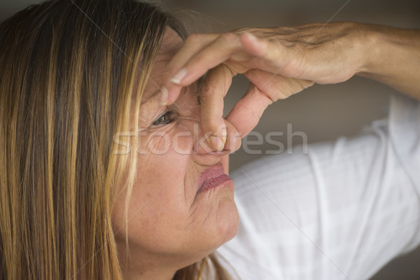 Woman annoyed by smelly air squeezing nose Stock photo © roboriginal