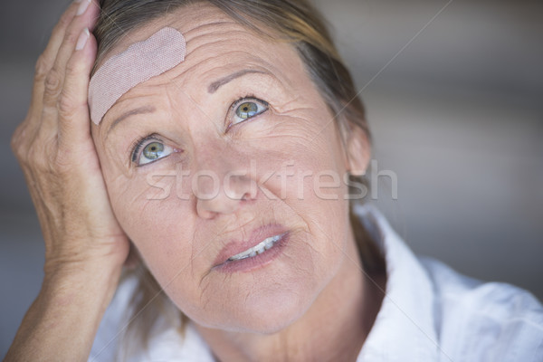 Woman with headache and band aid on forehead Stock photo © roboriginal