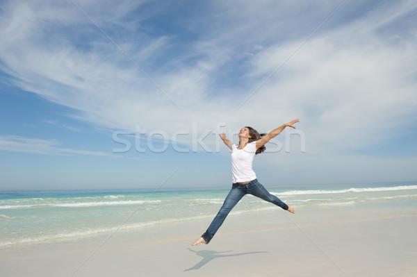 Woman jumping for joy at beach Stock photo © roboriginal