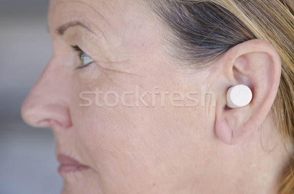 Stock photo: Woman blocking sound with ear plug