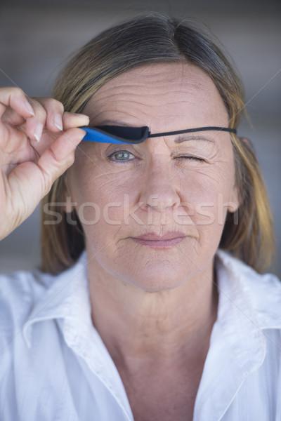 Confident woman lifting eye patch portrait Stock photo © roboriginal