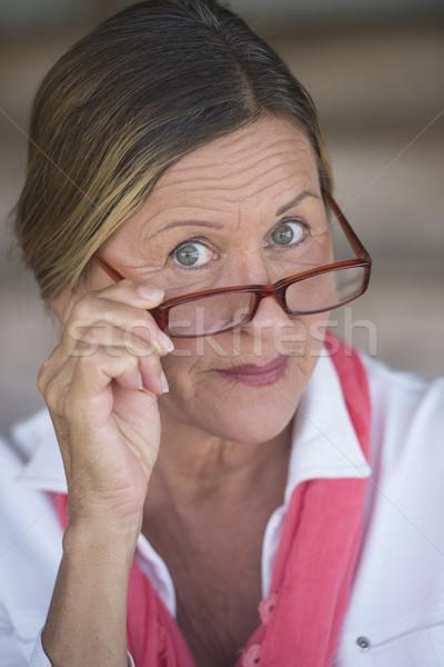 Curious mature business woman with glasses Stock photo © roboriginal