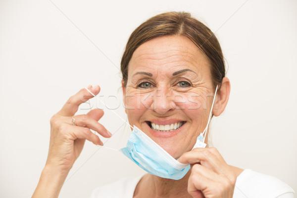 Cheerful female nurse with mask Stock photo © roboriginal